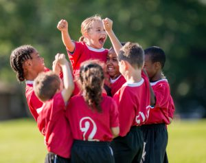A multi-ethnic soccer team full of elementary age children are cheering together after winning their game. They have their arms raised up in the air victoriously.